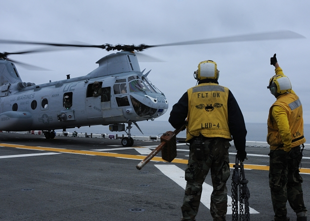 101016-N-1060K-021 PACIFIC OCEAN (Oct. 17, 2010) Sailors aboard the amphibious assault ship USS Boxer (LHD 4) remove chocks and chains from a CH-46 Sea Knight helicopter and signal the pilot for takeoff. Boxer and embarked Marines are conducting flight operations and work ups in preparation for a deployment early next year. (U.S. Navy photo by Mass Communication Specialist 3rd Class Anna Kiner/Released)