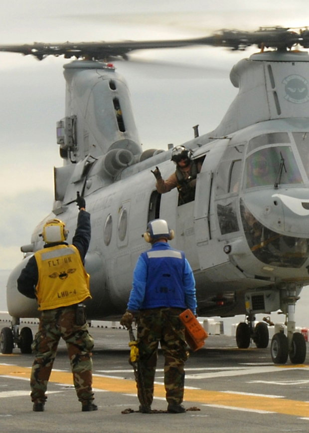 101018-N-1060K-017 PACIFIC OCEAN (Oct. 18, 2010) Aviation BoatswainÕs Mate 1st Class Roy Wiley signals to the pilots of a CH-46 Sea Knight helicopter to take off from the amphibious assault ship USS Boxer (LHD 4). Boxer is continuing to conduct flight operations and work ups until the ship deploys early next year. (U.S. Navy photo by Mass Communication Specialist 3rd Class Anna Kiner/Released)