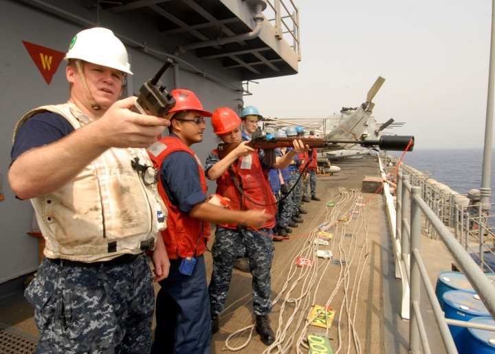 110703-N-DB458-010 GULF OF ADEN (July 3, 2011) BoatswainÕs Mate 2nd Class Jesse Dean, left, acts as safety observer while GunnerÕs Mate 2nd Class Alex Torres directs GunnerÕs Mate Seaman Apprentice Megan Halliburton as she prepares to fire a shot-line from the amphibious assault ship USS Boxer (LHD 4) to the Military Sealift Command fleet replenishment oiler USNS Tippecanoe (T-AO 199) during a replenishment at sea. Boxer is underway supporting maritime security operations and theater security cooperation efforts in the U.S. 5th Fleet area of responsibility. (U.S. Navy photo by Mass Communication Specialist 3rd Class Anna Kiner/Released)